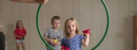 Lapsi heittää lennokin vanteen läpi.