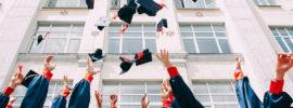 Opiskelijat heittävät hattuja ilmaan valmistujaisjuhlassa.