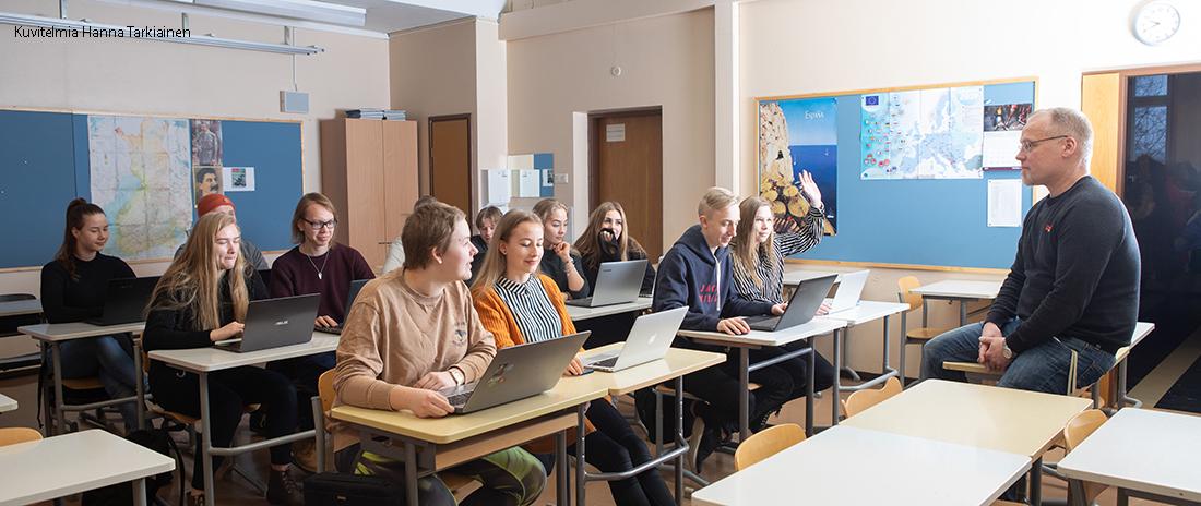 Oppilaita ja opettaja luokkahuoneessa. Oppilailla on edessään tietokoneet, opettaja istuu pöydällä. Yksi oppilaista viittaa.
